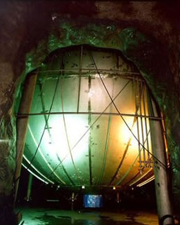 KamLAND consists of a weather balloon, 13 meters (43 feet) in diameter, filled with about a kiloton of liquid scintillator, a chemical soup that emits flashes of light when an incoming anti-neutrino collides with a proton. These light flashes are detected by a surrounding array of 1,879 photomultiplier light sensors which convert the flashes into electronic signals that computers can analyze.